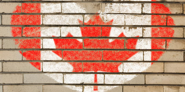 heart shaped flag in colors of Canada on brick wall