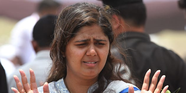 BEED, INDIA - JUNE 4: Daughter Pankaja Munde of late BJP leader Gopinath Munde during his funeral at Parali on June 4, 2014 in Beed, India. Munde, 64, Union Rural Development Minister, was yesterday killed in a road accident in Delhi while he was on way to Parli for a felicitation following his own and BJP's resounding victory in the Lok Sabha elections, which saw him re-elected for a second time from Beed. (Photo by Anshuman Poyrekar/Hindustan Times via Getty Images)