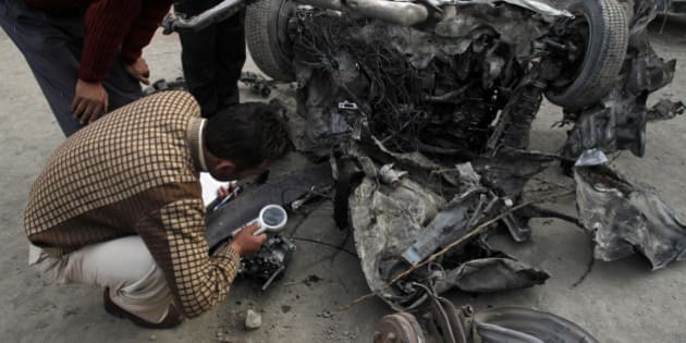 Indian police officers examine the wreckage of a car destroyed in an explosion in Bijbehara town, some 28 miles (45 kilometers) south of Srinagar India,Thursday, March 22, 2012. A bomb exploded Thursday in a car outside the main city of Indian-controlled Kashmir, killing the driver and wounding at least 23 other people in what police said may have been an accident involving suspected rebels. (AP Photo/Mukhtar Khan)
