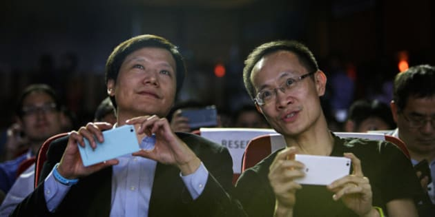 Billionaire Lei Jun, chairman and chief executive officer of Xiaomi Corp., left, and Bin Lin, president and co-founder, hold their smartphones during a news conference in New Delhi, India, on Thursday, April 23, 2015. Xiaomi unveiled the multi-language Mi 4i smartphone for India as China's largest smartphone maker adds new products to its biggest export market. Photographer: Kuni Takahashi/Bloomberg via Getty Images
