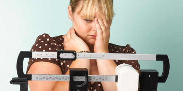 Obese teenager on scales concerned the result.