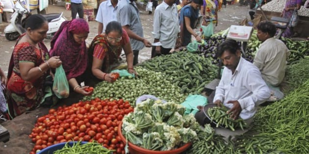 Indians buy vegetables at a market in Ahmadabad, India, Tuesday, Oct. 14, 2014. India's benchmark inflation rate fell to a five year low of 2.4 percent in September as food and vegetable prices dropped, the Commerce Ministry said Tuesday. (AP Photo/Ajit Solanki)