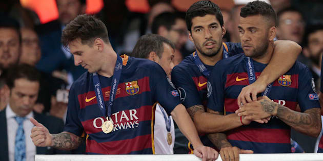 Barcelona's Lionel Messi, Luis Suarez and Dani Alves, from left to right, wait for the trophy after winning the UEFA Super Cup soccer match between FC Barcelona and Sevilla FC at the Boris Paichadze Dinamo Arena stadium, in Tbilisi, Georgia, on Wednesday, Aug. 12, 2015. Barcelona won 5-4. (AP Photo/Ivan Sekretarev)