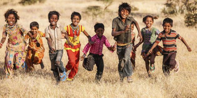 'Group of running happy Gypsy Indian children - desert village, Thar Desert, Rajasthan, India.'