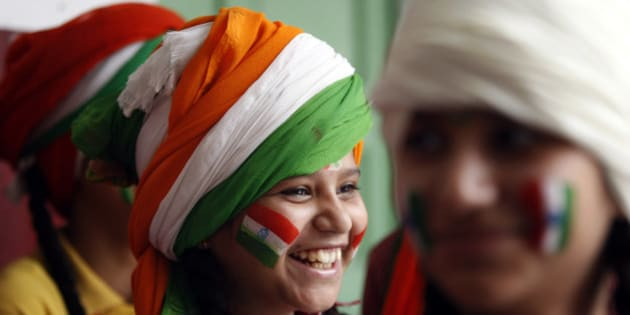 A girl, with her face painted in tricolor Indian flag, smiles as she waits to perform during celebrations in a school on the eve of Independence Day in Jammu, India, Friday, Aug. 14, 2015. India commemorates its Independence in 1947 from British colonial rule, on August 15. (AP Photo/Channi Anand)