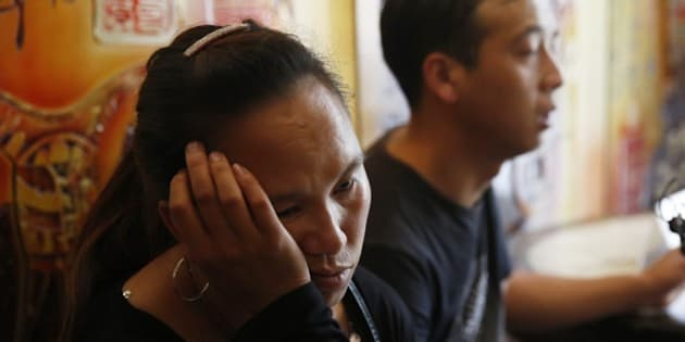 A family member (L) of missing firefighters mourns after being barred from a press conference in Tianjin on August 15, 2015. Furious, frustrated and fearful, relatives of the missing in giant explosions in Tianjin besieged officials on August 15 demanding answers on their loved ones fates- only for security to intervene instead.    CHINA OUT     AFP PHOTO        (Photo credit should read STR/AFP/Getty Images)