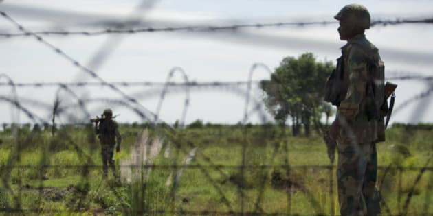 India's Border Security Force (BSF) soldiers patrol near the India-Pakistan international border fencing at Garkhal, about 35 kilometers (22 miles) west of Jammu, India, Monday, Sept. 16, 2013. Pakistani troops fired at Indian positions along the Line of Control in the Poonch district of Jammu and Kashmir drawing retaliation from Indian troops Sunday, according to local reports. (AP Photo/Channi Anand)