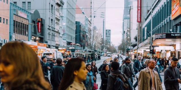 Commuters outside Flinders Street Station cross the road on the croner of flinders street and Elizabeth Street Melbourne Victoria Australia.