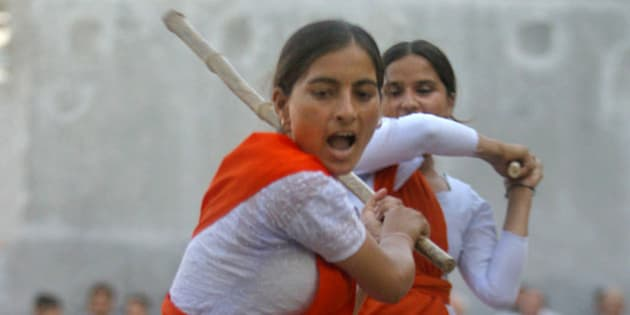 Madhu, a member of Durga Vahini, the womens wing of Hindu nationalist group Rashtriya Swayamsevak Sangh (RSS) or National Volunteers Association, performs a self-defense exercise with a stick on the outskirts of Jammu, India, Friday, June 18, 2004. The RSS organized a seven-day camp for self-defense training for its women cadres belonging to militancy-affected areas that ended Friday. (AP Photo/Channi Anand)