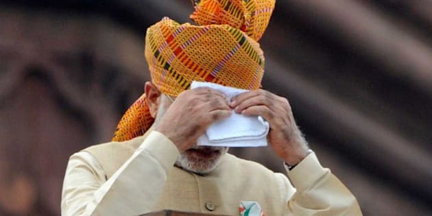 NEW DELHI, INDIA - AUGUST 15: Prime Minister Narendra Modi wipes his face as he addresses the nation from the rampart of historical Red Fort on the occasion of Independence Day celebration on August 15, 2015 in New Delhi, India. In his address to the nation from Red Fort, PM Modi spoke about the progress of various social security schemes launched by his government. He said efforts to bring back black money stashed abroad are on, while stressing that there's no place for casteism or communalism in India. Modi repeatedly referred to the central role of the country's one billion-plus population - which he dubbed 'Team India' - in his government's development plans, saying the people alone will take India to new heights. Modi, who spoke without the protection of a bulletproof shield, said his government had accepted the demand for OROP in principle but did not commit himself to a timeframe for rolling out the scheme. Modi warned that corruption was eating away at India 'like a termite' as he used an Independence Day speech to pledge his commitment to eradicating graft and poverty. (Photo by Mohd Zakir/Hindustan Times via Getty Images)