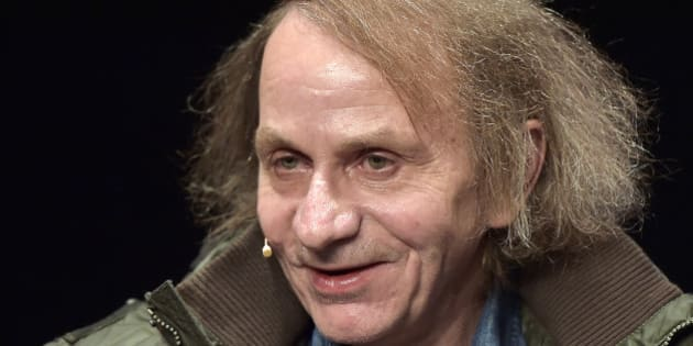 "French novelist and poet Michel Houellebecq smiles towards the audience prior to a reading of his latest book in Cologne, Germany, Monday, Jan. 19, 2015. The controversial author appears in public for the first time after his book ""Soumission"" (submission) was published on the day of the Charlie Hebdo shooting in Paris. A cartoon of Houellebecq was published on the magazine's cover page that day, giving attention to his book, describing a future France where a Muslim president is ruling the country according to Islamic law. (AP Photo/Martin Meissner)"