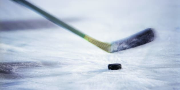 View of an ice hockey stick about to hit the puck