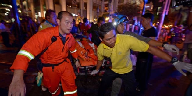 Thai rescue workers carry an injured person after a bomb exploded outside a religious shrine in central Bangkok late on August 17, 2015 killing at least 10 people and wounding scores more.  Body parts were scattered across the street after the explosion outside the Erawan Shrine in the downtown Chidlom district of the Thai capital.         AFP PHOTO / PORNCHAI KITTIWONGSAKUL        (Photo credit should read PORNCHAI KITTIWONGSAKUL/AFP/Getty Images)