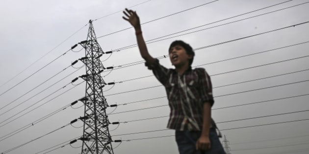 An Indian boy gestures as he stands near high tension electricity tower on a roadside in New Delhi, India, Wednesday, Aug. 1, 2012. Factories and workshops across India were up and running again Wednesday, a day after a major system collapse led to a second day of power outages and the worst blackout in history leaving an estimated 620 million people without electricity. (AP Photo/Kevin Frayer)