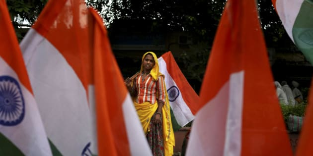 A woman laborer sells Indian flags outside the venue of an anti-corruption protest ahead of Indian Independence Day in New Delhi, India, Tuesday, Aug. 14, 2012. India celebrates its 1947 independence from British colonial rule on Aug. 15. (AP Photo/Kevin Frayer)