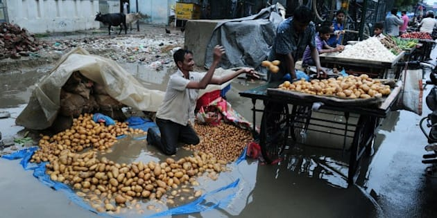 An Indian vegetable vendor removes potatoes from his tarpaulin after heavy monsoon rains inundated a roadside market in Allahabad on August 16, 2015.     AFP PHOTO/ SANJAY KANOJIA        (Photo credit should read Sanjay Kanojia/AFP/Getty Images)