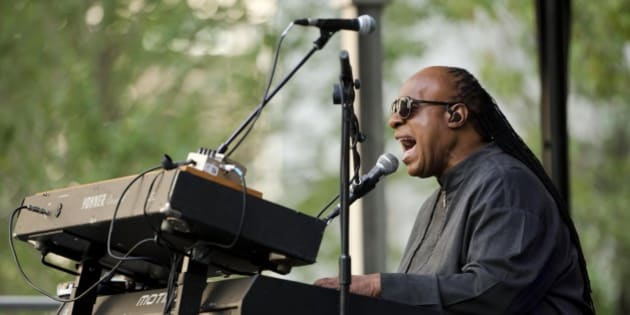 "Musician Stevie Wonder performs during a free pop-up concert Monday, Aug. 17, 2015, outside City Hall in Philadelphia. The concert is part of a news conference promoting Wonder's ""Songs in the Key of Life Performance"" tour.  (AP Photo/Matt Rourke)"