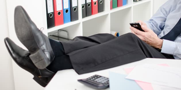 Relaxed businessman using his smartphone at office