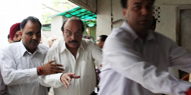 Indian real estate businessman businessman Gopal Ansal (C) is escorted to the prison at the Patiala House Court in New Delhi on September 11, 2008. Real estate barons Sushil and Gopal Ansal surrendered before a Delhi court in compliance with a Supreme Court order cancelling their bail in the case of the Uphaar cinema fire tragedy which claimed 59 lives.    AFP PHOTO/MANAN VATSYAYANA (Photo credit should read MANAN VATSYAYANA/AFP/Getty Images)