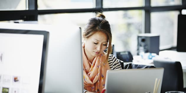 Businesswoman sitting at desk in high tech startup office working on laptop