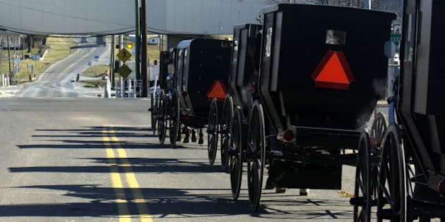 It was slow going for Old Order Mennonite carriages returning from church Sunday, Jan. 12, 2003, in Dayton, Va. The stoplight's magnetic detector at Va. 42 and Huffman Drive doesn't register the horse-drawn buggies, so traffic can back up  at the intersection. Transportation officials say they may have a $5 solution to a $130,000 traffic problem by adding a copper wire to the undercarriage of the buggies. Tests are underway. (AP Photo/The Daily News-Record, Allen Litten)