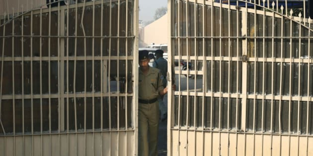 FILE- In this March 11, 2013 file photo, an Indian police officer prepares to close one of the gates at Tihar Jail, the largest complex of prisons in South Asia, in New Delhi, India. India's Tihar Jail is a land of bakeries and carpentry shops, where inmates compete in music contests, take classes and perform intensive Buddhist meditation as part of their rehabilitation.  Tihar Jail is also a vast, overcrowded facility, crammed with people awaiting trial who sleep on concrete floors, face daily threats from other prisoners and are shaken down for bribes from their poorly paid jailers, according to human rights lawyers and former inmates there. The two sides of India's most famous jail emerged this week when a man accused in the notorious rape of a woman aboard a New Delhi bus was found dead in his cell, either a suicide, according to jail officials, or a victim of foul play, according to his family. (AP Photo/Saurabh Das)