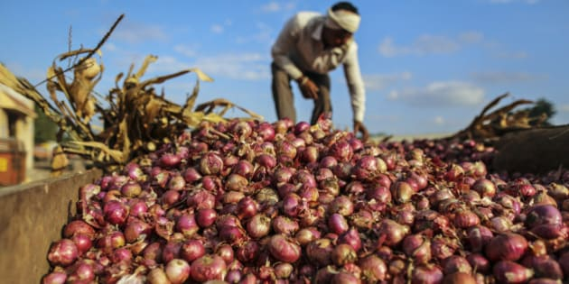 A farmer arranges onions in a tractor trailer at the Agriculture Produce Market Committee (APMC) wholesale market in Umrana, Maharashtra, India, on Tuesday, Nov. 11, 2014. Consumer prices rose 5.52 percent in October from a year earlier, the slowest pace since the index was created in January 2012, according to government data released Nov. 12, as the government commits to continuing reforms in food markets that will improve supply and keep inflation low. Photographer: Dhiraj Singh/Bloomberg via Getty Images