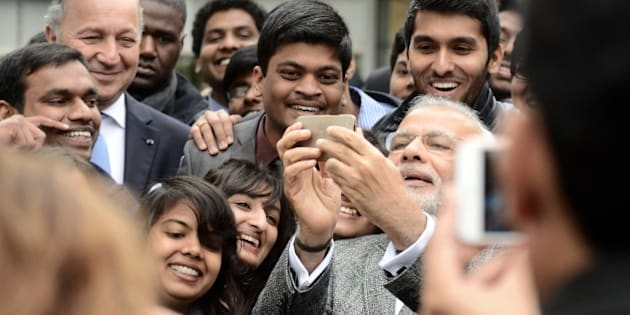 Indian Prime Minister Narendra Modi (C) takes a selfie with a delegation of Indian people studying in the French Midi-Pyrenees region next to French Foreign Affairs Minister Laurent Fabius (L) as he visits the National center for space studies (CNES) on April 11, 2015 in Toulouse. Modi wraps up his two-day trip to France with a visit to the Airbus headquarters after he said on the eve he had asked France to supply his air force with 36 Rafale fighter jets, after years of wrangling over the deal. AFP PHOTO /  REMY GABALDA        (Photo credit should read REMY GABALDA/AFP/Getty Images)