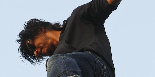 Bollywood star Shah Rukh Khan balances himself on a fence to greet fans on his 48th birthday, outside his house in Mumbai, India, Saturday, Nov. 2, 2013. (AP Photo/Rajanish Kakade)