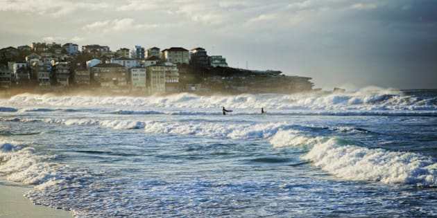 Bondi Beach, Sydney, Australia, on a fine winter morning with good surf, two surfers just walking out into the waves.