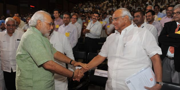 Gujarat state Chief Minister Narendra Modi (L) and  Indian Union Agriculture Minister Sharad Pawar greet each other before the launch of the 'Mission Milk' National Dairy Plan at the National Dairy Development Board, NDDB, Amul in Anand town, some 75 kms from Ahmedabad, on April 19, 2012. Indian Union Agriculture Minister Sharad Pawar launched the National Dairy Plan in the presence of Gujarat state Chief Minister, Narendra Modi. AFP PHOTO / Sam PANTHAKY (Photo credit should read SAM PANTHAKY/AFP/Getty Images)