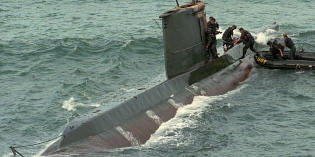 South Korean soldiers take to a North Korean submarine which was found stranded on a reef on South Korea's east coast at Kangnung, northeast of Seoul, Wednesday, Sept. 18, 1996. One North Korean intruder was captured and 11 others were found dead after abandoning the submarine according to the Defense Ministry. (AP Photo/Ahn Young-joon)