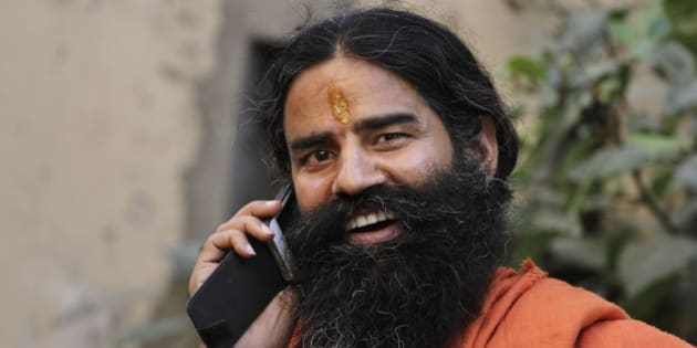 Indian yoga guru Baba Ramdev talks on a mobile phone, as he leaves after a press conference in Ahmadabad, India, Monday, Oct. 29, 2012. (AP Photo/Ajit Solanki)
