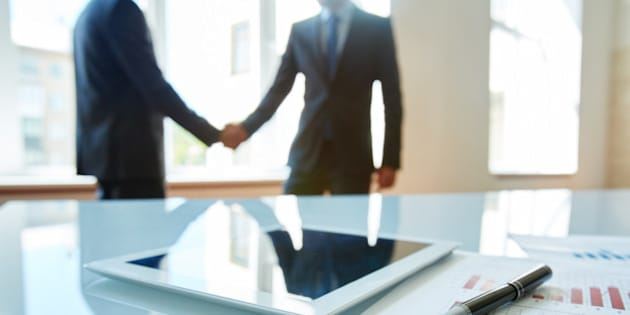 Business objects at workplace with handshaking partners on background