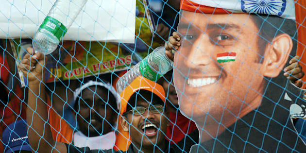 Kochi, INDIA:  Indian supporters wave a cut out of player Mahendra Singh Dhoni during the fourth One-Day International match between India and England at The Jawaharlal Nehru Stadium, in Kochi, 06 April 2006.  India won by 4 wickets to clinch the seven-match one-day series 4-0.   AFP PHOTO/Christophe ARCHAMBAULT    (Photo credit should read CHRISTOPHE ARCHAMBAULT/AFP/Getty Images)