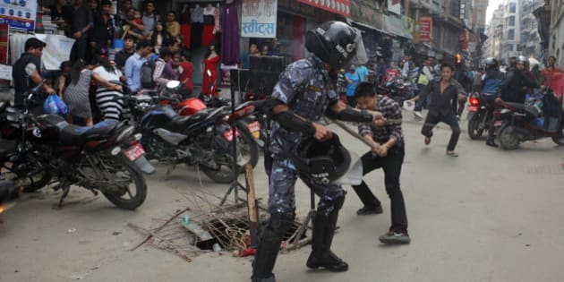 Nepalese protesters clash with a policeman during a torch rally in Kathmandu, Nepal, Saturday, Aug. 15, 2015. Supporters of small opposition parties protested to oppose the constitution drafting process. (AP Photo/Niranjan Shrestha)