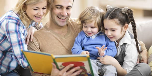 Smiling parents reading a book to their little children.