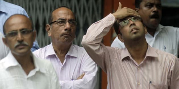 MUMBAI, INDIA - AUGUST 24: Anxious onlookers watch share prices on a screen outside the Bombay Stock Exchange on August 24, 2015 in Mumbai, India. Sensex crashed over 1700 points or 6.22 per cent in pre-close trade with the investor wealth down by over Rs. 7 lakh crore with nearly Rs. 4 lakh crore lost in an hour. (Photo by Kunal Patil/Hindustan Times via Getty Images)