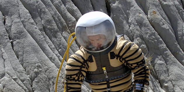 University of North Dakota Space Studies graduate studen Fabio Sau tests out a experimental planetary space suit in the North Dakota Badlands near Fryburg, N.D., on Saturday, May 6, 2006. Sau is the guinea pig for an experimental Mars space suit that he and about 40 other students from five North Dakota schools developed under a $100,000 grant from NASA. The suit was formally unveiled Saturday in a craterlike area surrounded by buttes in the North Dakota Badlands, the highly eroded landscape that researchers say resembles Martian terrain.  In this test the outer blue covering of the suit has been removed. (AP Photo/Will Kincaid)