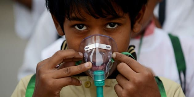 An Indian schoolchild adjusts his facemask before the start of an event to spread awareness of the problem of air pollution in New Delhi on June 4, 2015, on the eve of World Environment Day. The Indian government is under intense pressure to act after the World Health Organisation last year declared New Delhi the world's most polluted capital. At least 3,000 people die prematurely every year in the city because of air pollution, according to a joint study by Boston-based Health Effects Institute and Delhi's Energy Resources Institute. World Environment Day is marked anually on June 5. AFP PHOTO/MONEY SHARMA        (Photo credit should read MONEY SHARMA/AFP/Getty Images)