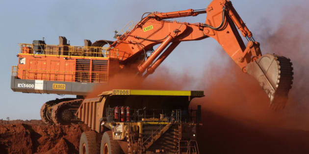 A digger loads ore onto a dump truck at the Delta 2 mine pit at Hancock Prospecting Pty's Roy Hill Mine operations under construction in the Pilbara region, Western Australia, on Thursday, Nov. 20, 2014. Gina Rinehart, the Asia-Pacific's richest woman, is set to start exports in September from her new A$10 billion ($8.6 billion) iron ore mine undeterred by prices trading near five-year lows and forecast to extend losses. Photographer: Philip Gostelow/Bloomberg via Getty Images