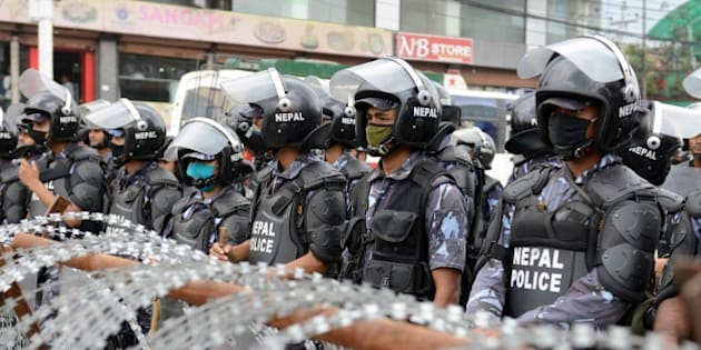 Nepalese riot police stand guard near the Constitutional Assembly building during a protest by Nepalese Dalit activists demanding equal rights in the new constitution in Kathmandu on August 5, 2015. Lawmakers tabled a draft in parliament in June shortly after bickering political parties struck an historic deal on the long-awaited charter, spurred to negotiation by an earthquake in March that killed more than 8,800 people. AFP PHOTO / Prakash MATHEMA        (Photo credit should read PRAKASH MATHEMA/AFP/Getty Images)
