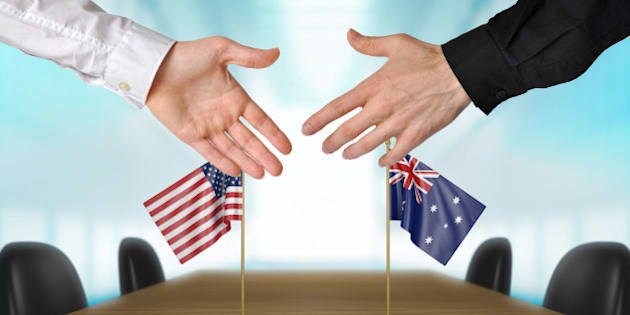 Two diplomats from United States and Australia  extending their hands for a handshake on an agreement between the countries.
