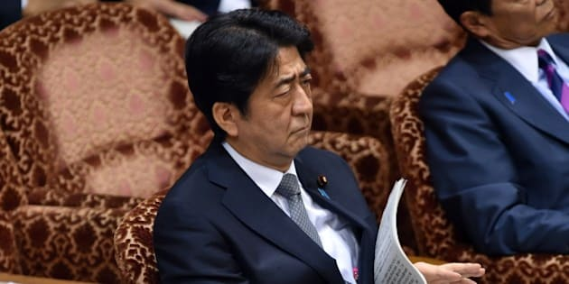 Japanese Prime Minister Shinzo Abe listens to a question by an opposition lawmaker at the Upper House's budget committee session at the National Diet in Tokyo on August 24, 2015. Abe will not visit China next month as he faces parliamentary backlash over his bid to expand the role of the military. Earlier this month, Abe repeated a desire to meet Chinese President Xi Jinping in early September, but was not expected to attend a huge Beijing military show of strength to commemorate the 70th anniversary of Japan's defeat in World War II.  AFP PHOTO / Yoshikazu TSUNO        (Photo credit should read YOSHIKAZU TSUNO/AFP/Getty Images)
