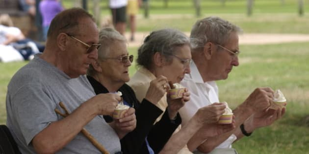 Four pensioners sat on a park bench eating ice cream, Stratford upon Avon, UK. (Photo By: Education Images/UIG via Getty Images)