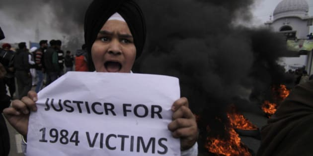 A young Sikh protestor holds a placard as dozens of others burn tires during a protest against Congress party leader Rahul Gandhi for his recent remark on the country's 1984 anti-Sikh riots, in Jammu, India, Sunday, Feb. 2, 2014. Rahul Gandhi in a recent television interview refused to apologize for the riots that killed more than 3,000 Sikhs saying he was not in operation in the Congress party in 1984. Top Congress party leaders have been accused of inciting mobs during the violence that followed the assassination of Prime Minister Indira Gandhi by her Sikh bodyguards. (AP Photo/Channi Anand)