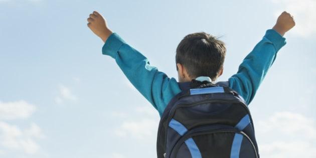 Boy (6-7) wearing backpack punching air