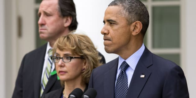 Neil Heslin, father of Newtown victim Jesse Lewis, left, and former Rep. Gabby Giffords, D-Ariz.,  stand with President Barack Obama as he pauses while surrounded by Newtown families and speaking about measures to reduce gun violence, in the Rose Garden of the White House, in Washington, Wednesday, April 17, 2013. (AP Photo/Jacquelyn Martin)