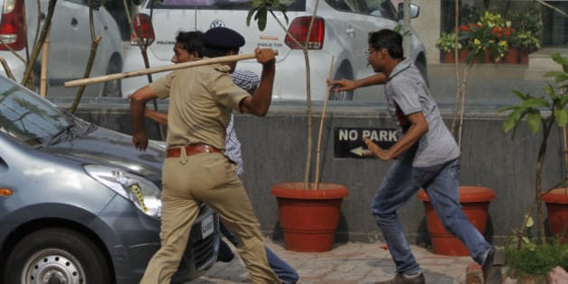 An Indian policeman uses a baton to disperse protesters during a clash between two groups in Ahmadabad, India, Tuesday, Aug. 25, 2015. Clashes were reported in parts of the city after tens of thousands of members Gujarat's Patel community held a rally demanding affirmative action for better access to education and employment. (AP Photo/Ajit Solanki)