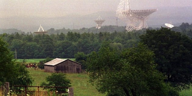 TO GO WITH STORY TITLED RADIO TELESCOPE--The Robert C. Byrd Telescope and its smaller companions at the rural National Radio Astronomy Observatory at Green Bank, W.Va., loom above the trees July 27, 2001. The Byrd telescope and its companions collect radio waves and use them to study galaxies, pulsars, planets, asteroids and forming stars. (AP Photo/Chris Dorst)